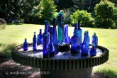 Cobalt bottles, arranged on a glass and rusty metal table. They make the shade seem even cooler, with the calming color.